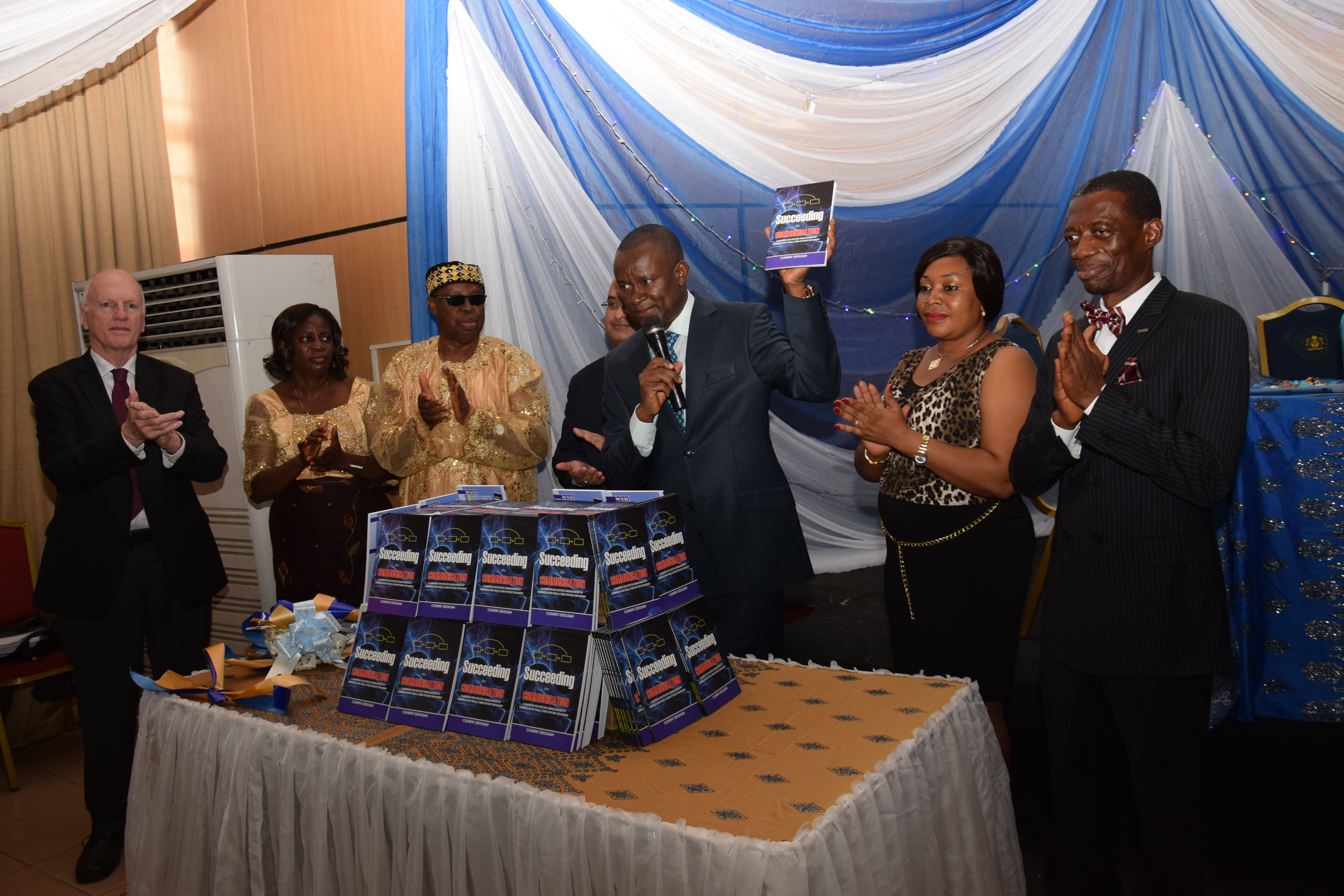 Sen. John Enoh presents the book, while others including the author appreciate the occasion